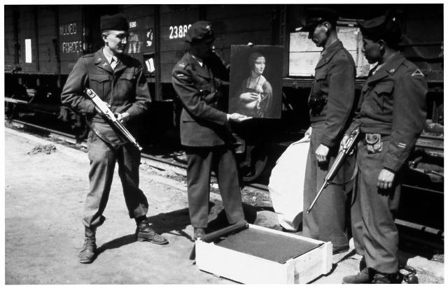 Der polnische Kunsthistoriker Karol Estreicher präsentiert 1946 Die Dame mit dem Hermelin auf dem Krakauer Hauptbahnhof zusammen mit dem US-amerikanischen MFAA-Leutnant Frank P. Albright und zwei nicht identifizierten Gis. Foto Lynn Nicholas, Quelle: www.rapeofeuropa.com