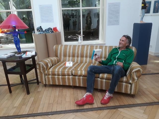 """Volker März auf dem Sofa mit dem """"Horizontalisten"""" in der Hand, Georg-Kolbe-Museum, 2018. Foto © Urszula Usakowska-Wolff"""